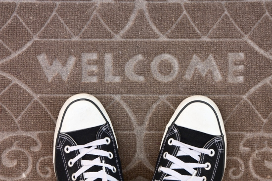 Welcome mat with black and white sneakers